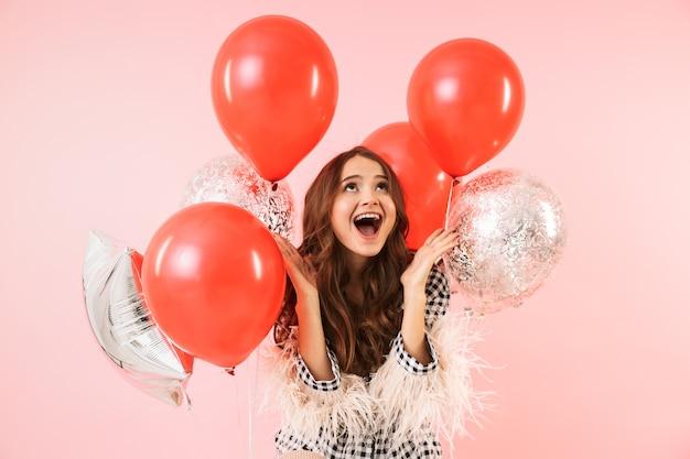 Hermosa joven vistiendo una chaqueta que se encuentran aisladas sobre fondo rosa, celebrando, sosteniendo un montón de globos