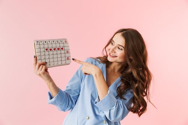 Hermosa joven vistiendo pijamas que se encuentran aisladas sobre fondo rosa, mostrando el calendario menstrual
