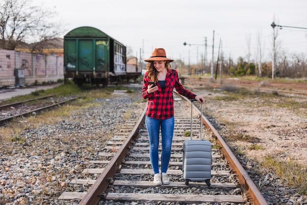 Hermosa joven vistiendo ropa casual, caminando por el ferrocarril con maleta y teléfono móvil