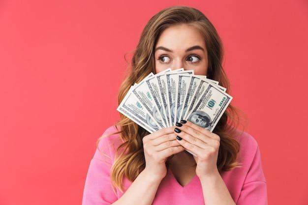 Hermosa joven vistiendo ropa casual que se encuentran aisladas sobre pared rosa, mostrando billetes de dinero