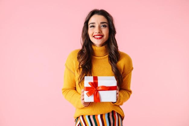 Hermosa joven vistiendo ropas coloridas que se encuentran aisladas sobre rosa, sosteniendo una caja de regalo