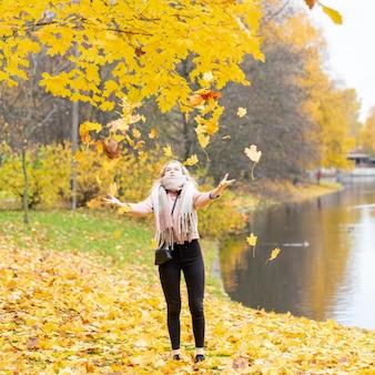 Hermosa joven vomita hojas de otoño. atractiva joven está descansando, jugando
