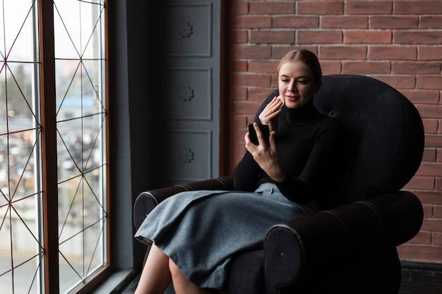 Hermosa joven womanon sofá con móvil