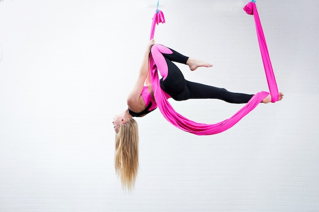 Hermosa joven yoga antigravedad en una hamaca de seda rosa mientras se hace.