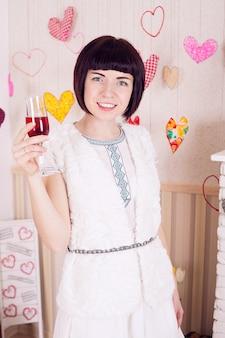 Hermosa jovencita bebiendo vino en el día de san valentín