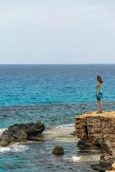 Hermosa jovencita disfrutando de la brisa ligera del mar.