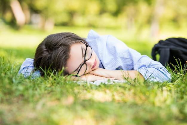 Hermosa jovencita duerme sobre el césped en el parque día soleado