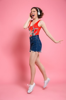 Hermosa jovencita emocional bailando y escuchando música.