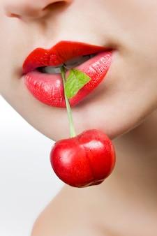 Hermosa jovencita isholding una cereza en los labios