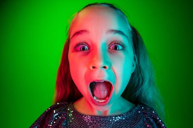Hermosa jovencita mirando sorprendido aislado en verde