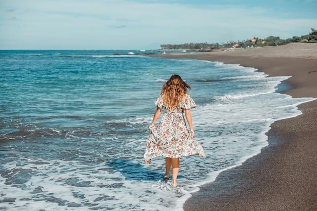 Hermosa jovencita posando en la playa, el océano, las olas, el sol brillante y la piel bronceada.