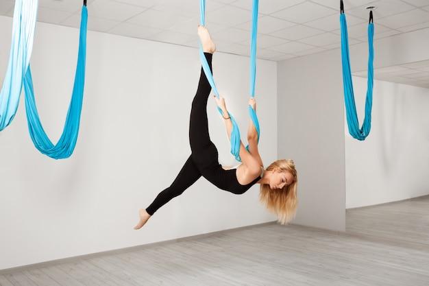Hermosa jovencita practicando yoga aéreo en el gimnasio.