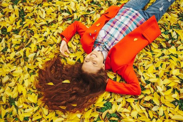 Hermosa jovencita rodeada de hojas de otoño