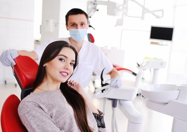 Hermosa jovencita en silla dental y dentista sonriendo a la cámara