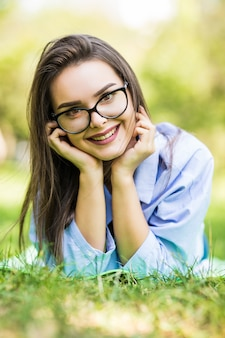 Hermosa jovencita soñadora recostada sobre la hierba en el parque