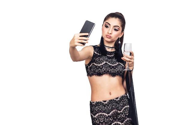 Hermosa jovencita sostiene una copa de champán y tomando selfie. aislado en blanco