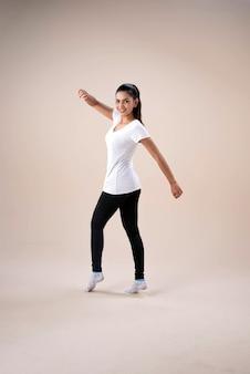 Hermosa jovencita vestida con ropa deportiva, de pie con los pies separados, arrodillarse, señalar con el dedo del pie hacia abajo, levantar las manos y girar ligeramente, bailar para hacer ejercicio, con un sentimiento feliz