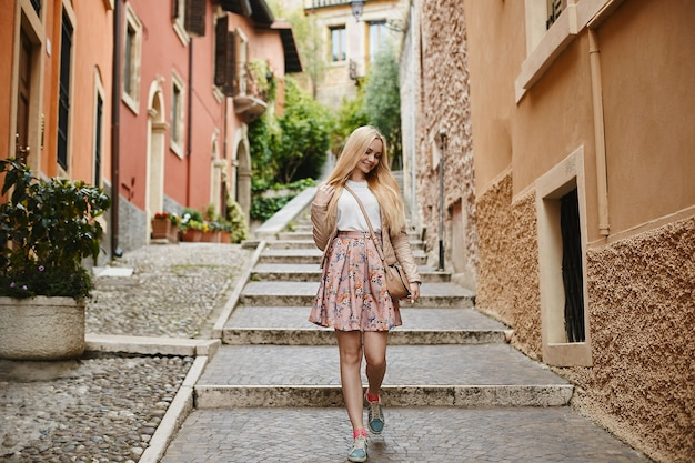 Hermosa y linda chica rubia modelo en falda rosa, blusa blanca y chaqueta de cuero