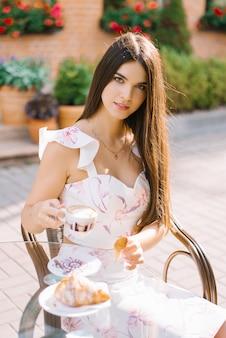 Hermosa linda chica sentada en una mesa en un café de la calle y tomando café. desayuno o almuerzo de una mujer bonita.