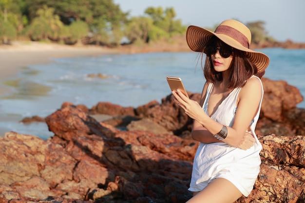 Hermosa y linda empresaria utilizando teléfono celular con gafas de sol y sombrero en la playa