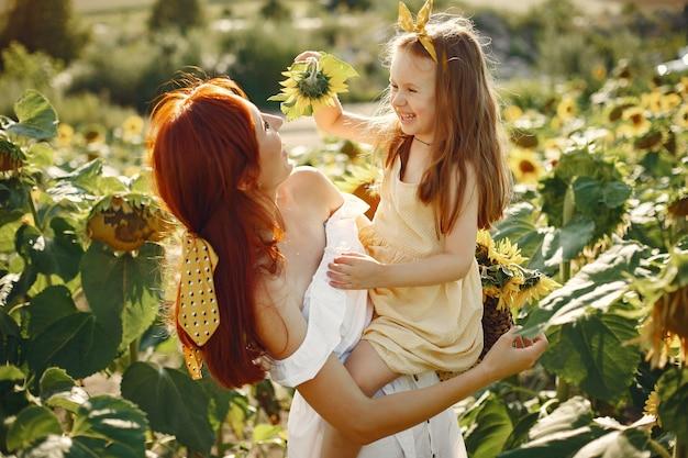 Hermosa y linda familia en un campo con girasoles