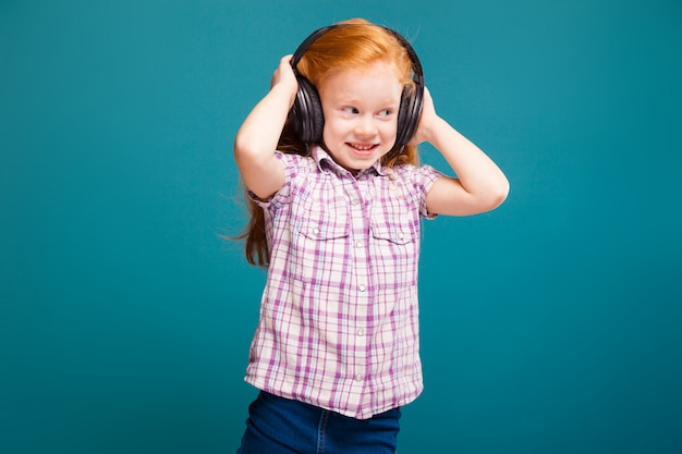 Hermosa y linda niña con camisa a cuadros y auriculares con cabello largo y rojo escucha musik