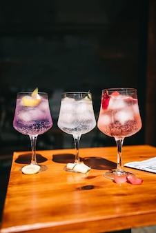 Hermosa línea de cócteles alcohólicos multicolores en una fiesta en la mesa de martini