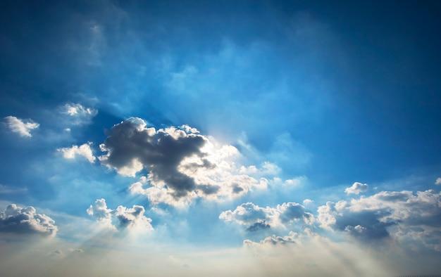 Hermosa luz del sol a través de nubes dramáticas contra el cielo azul