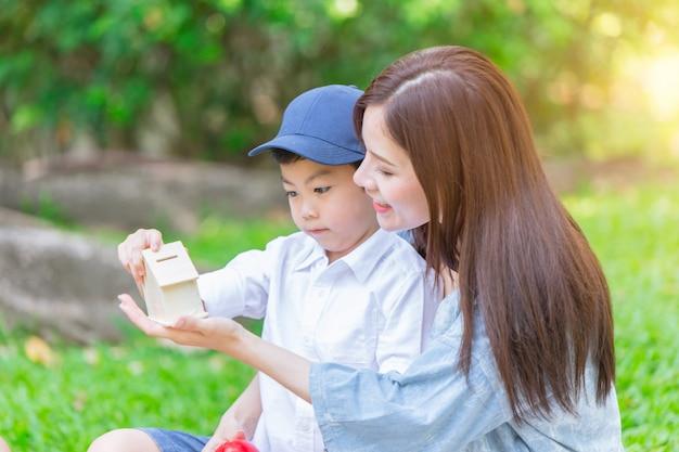 Hermosa madre asiática jugando con su encantador hijo en el parque verde