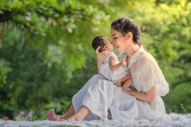 Hermosa madre y bebé en un parque asiático