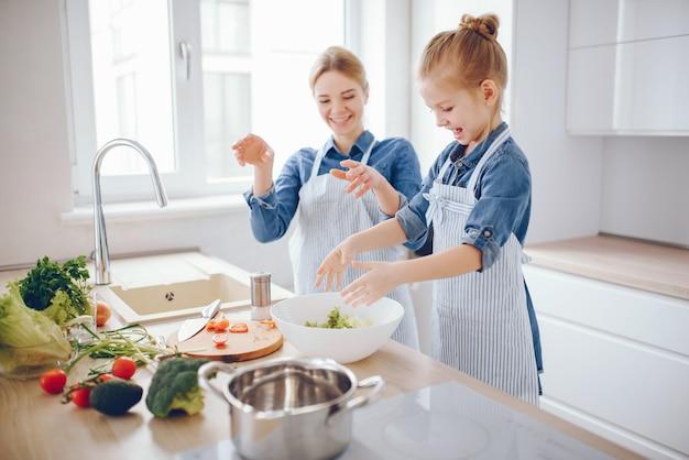 Hermosa madre con una camisa azul y un delantal está preparando una ensalada de vegetales frescos en casa