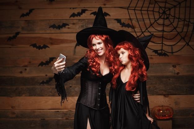 Hermosa madre caucásica y su hija con el pelo rojo largo en trajes de bruja tomando un selfie