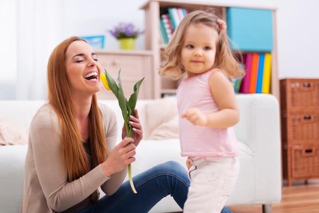 Hermosa madre disfrutando de la flor que recibió de su hija.