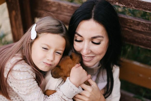 Hermosa madre e hija abrazan a su perrito marrón