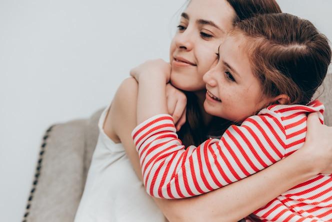 Hermosa madre e hija abrazando juntos en casa, concepto de familia