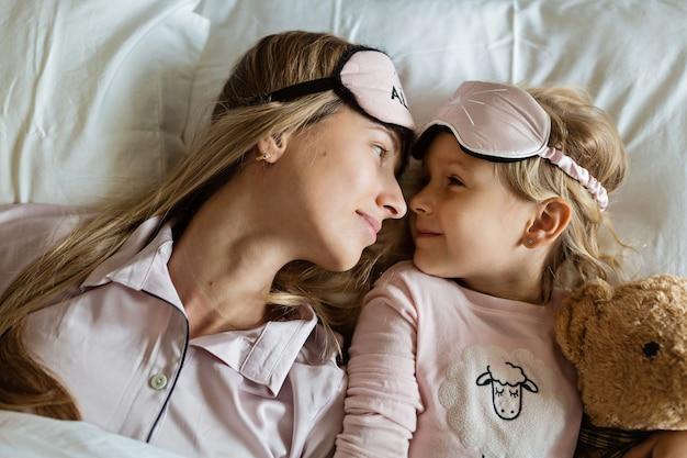 Hermosa madre e hija con cabello rubio acostado en su casa en la cama en pijama y con los ojos vendados
