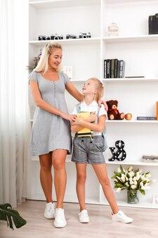Hermosa madre e hija linda se comunican. hija va a la escuela