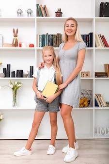 Hermosa madre e hija posando en casa antes de ir a la escuela