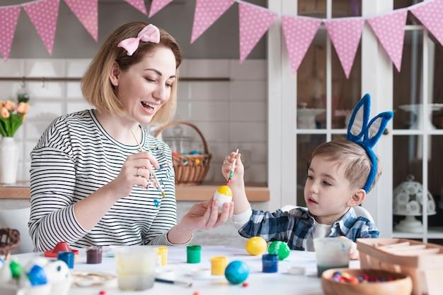 Hermosa madre enseñando a lindo niño a pintar huevos