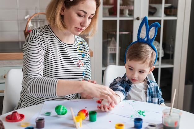 Hermosa madre enseñando a niño a pintar huevos