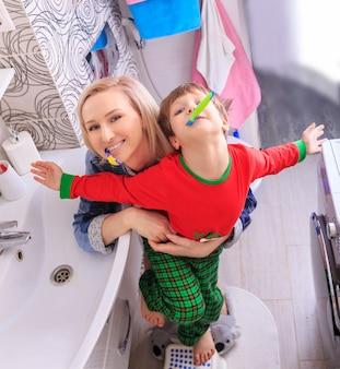 Hermosa madre feliz y pequeño hijo en bathrom cepillarse los dientes juntos