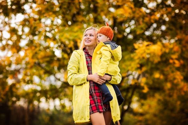 Hermosa madre con hijo en el parque otoño