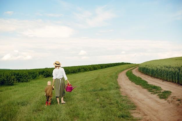 Hermosa madre con hijo pequeño en un campo de verano