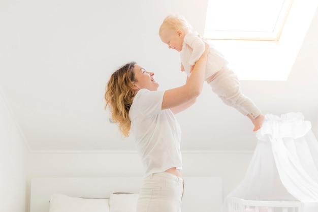 Hermosa madre jugando con bebé en casa