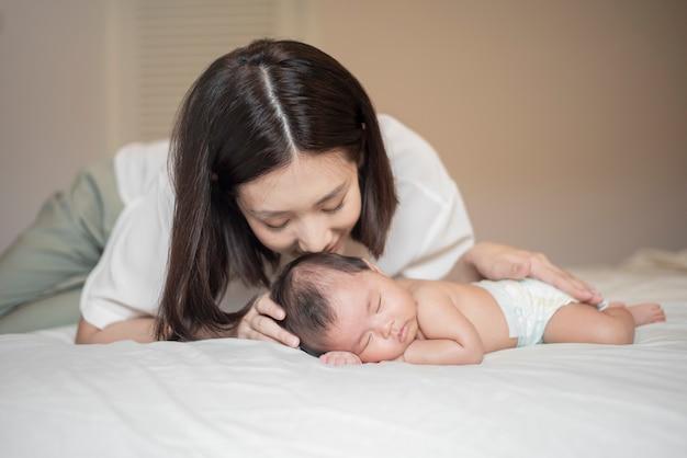 Hermosa madre está jugando con su bebé recién nacido en el dormitorio.
