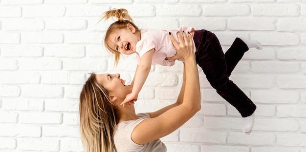 Hermosa madre jugando con su hija en casa