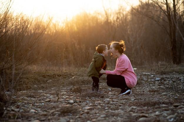Hermosa madre jugando con su hijo en la naturaleza contra la puesta de sol.