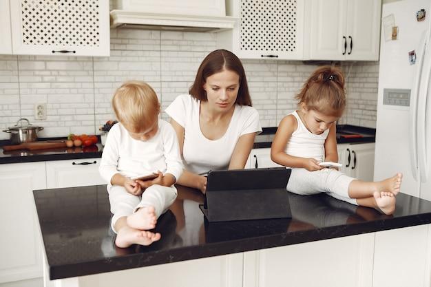 Hermosa madre con lindos hijos en casa en una cocina
