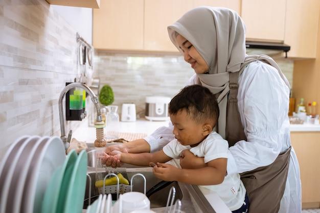 Hermosa madre musulmana lavar la mano de su hijo en el fregadero de la cocina