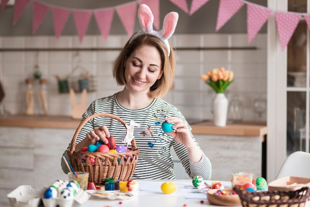Hermosa madre con orejas de conejo llenando la canasta con huevos